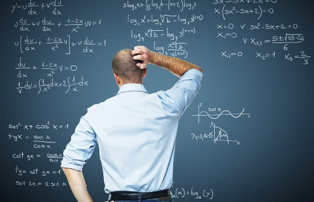 A taecher stands looking at calculations on a backboard